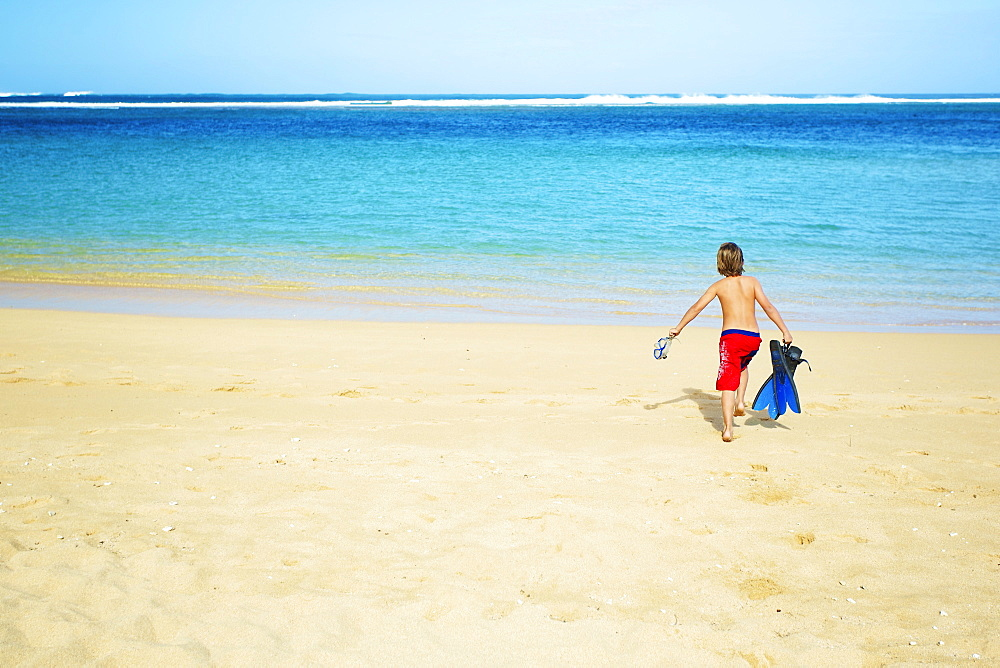A Boy Running Out To The Ocean Across The Beach With Snorkelling Gear, Kauai, Hawaii, United States Of America