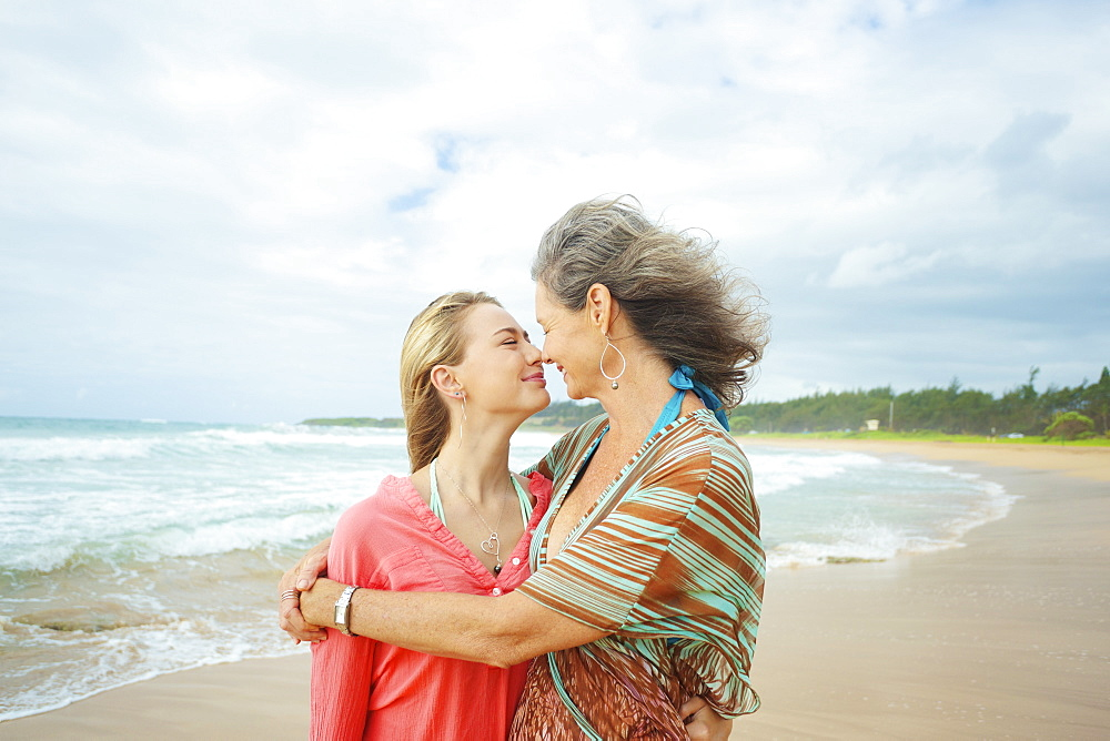 A Mother And Daughter Together On The Beach At The Water's Edge, Kauai, Hawaii, United States Of America