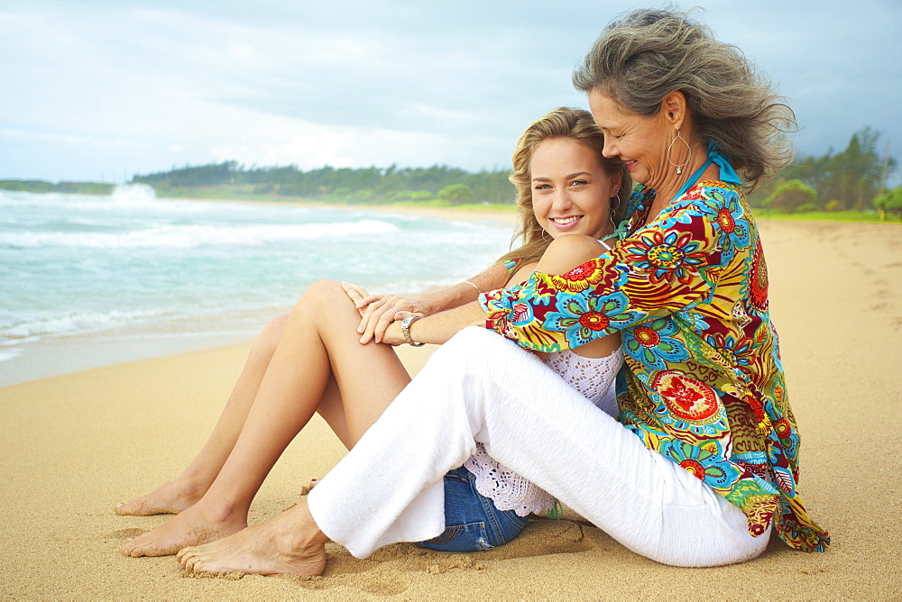 A Mother And Daughter Sitting Together On The Beach At The Water's Edge, Kauai, Hawaii, United States Of America