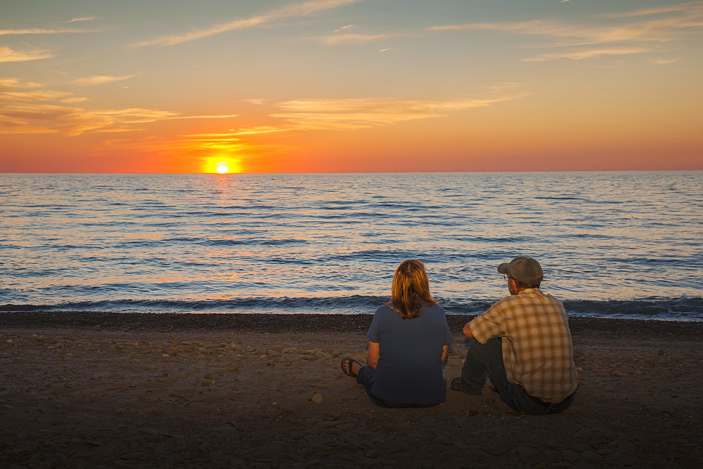 A Man And Woman Sit On A Beach Watching The Sunset On Lake Erie, Presque Isle State Park, Erie, Pennsylvania, United States Of America