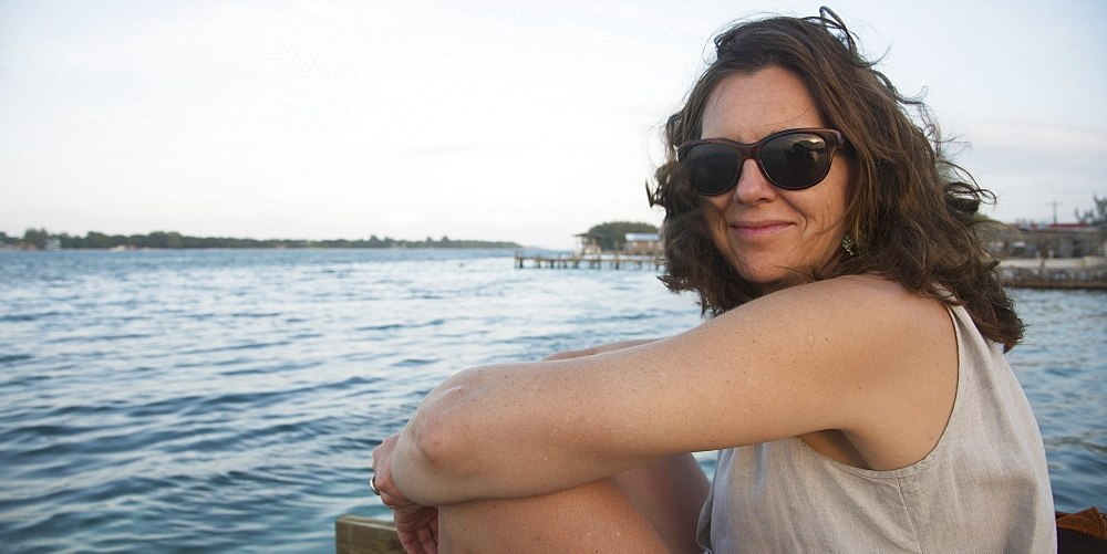 Portrait Of A Woman Sitting On The Water's Edge, Utila, Bay Islands, Honduras
