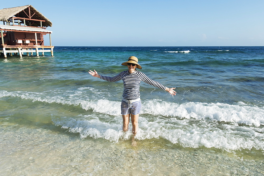 A Woman Stands In The Waves Beside A Hotel On The Coast, Utila, Bay Islands, Honduras