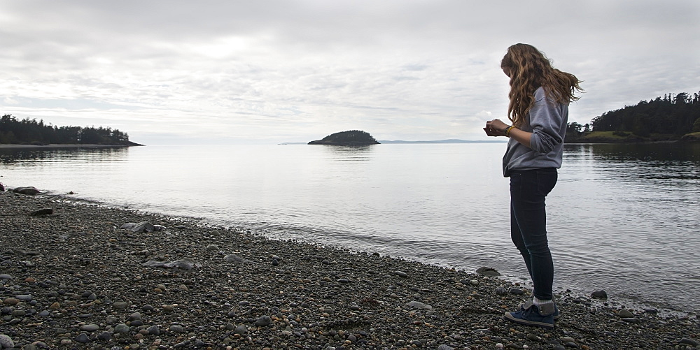 A Young Woman Stands On A Rocky Beach In Deception Pass State Park, Oak Harbor, Washington, United States Of America