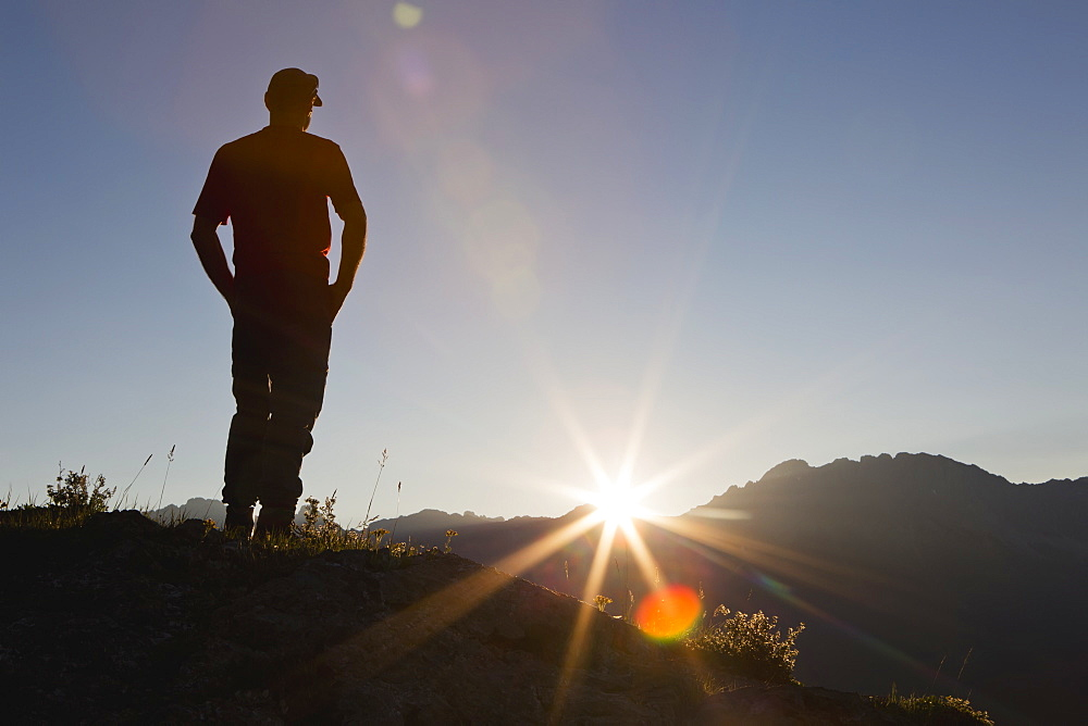 A Man Stands On A Ridge Overlooking The Landscape With Bright Sun Rays, Kananaskis, Alberta, Canada