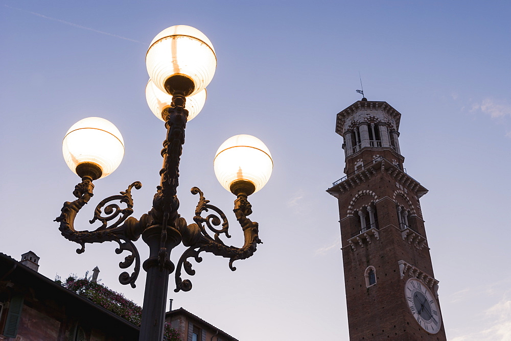 A Clock Tower And Illuminated Lamp Post In Piazza Delle Erbe At Dusk, Verona, Italy