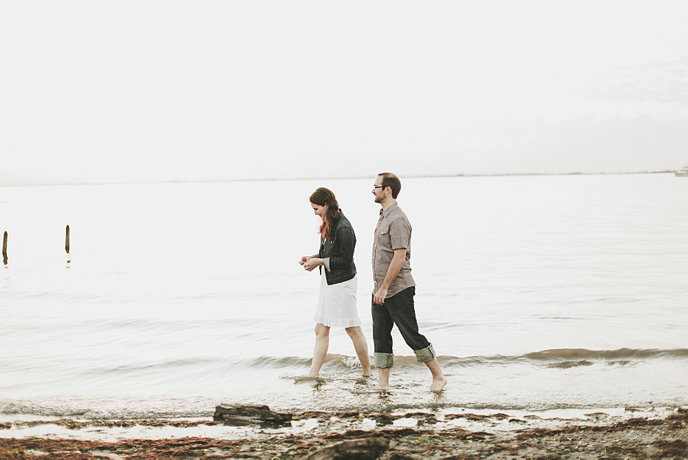 A Couple Walking Barefoot Along The Water's Edge, Crescent Beach, British Columbia, Canada
