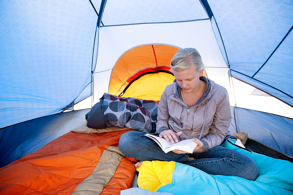A Young Woman Reading A Book Inside A Tent, California, United States Of America