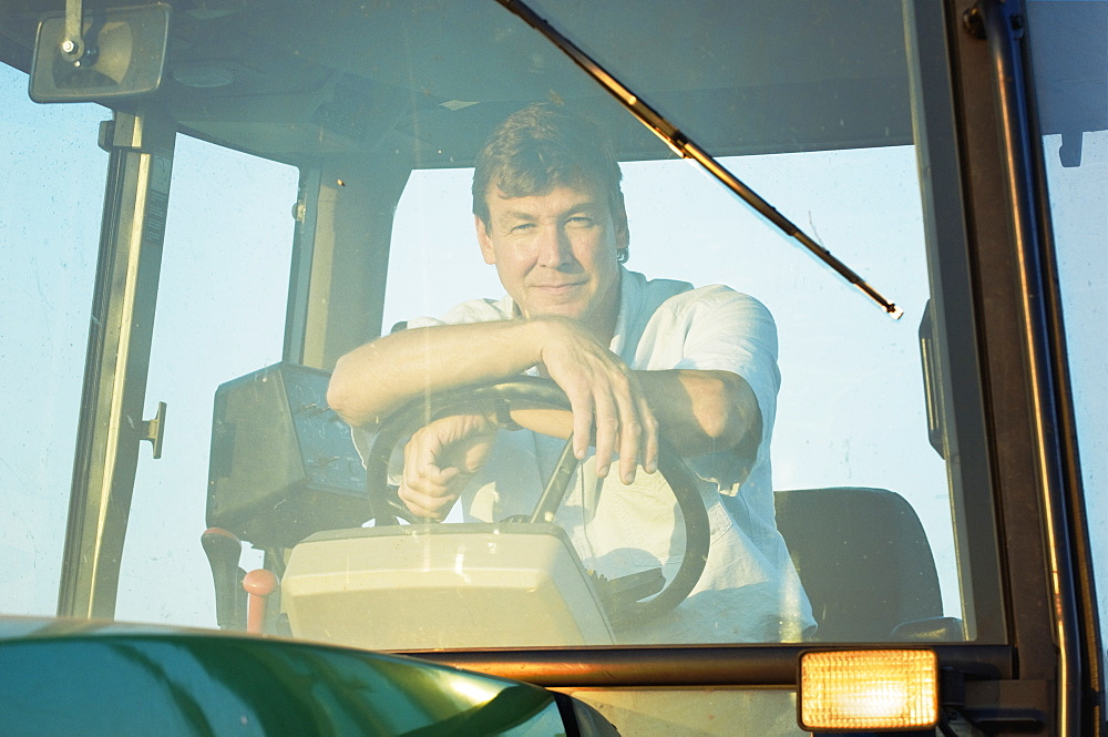 Agriculture - A farmer sitting in the cab of his John Deere tractor in late afternoon sunlight / near Hoffman, Minnesota, USA.