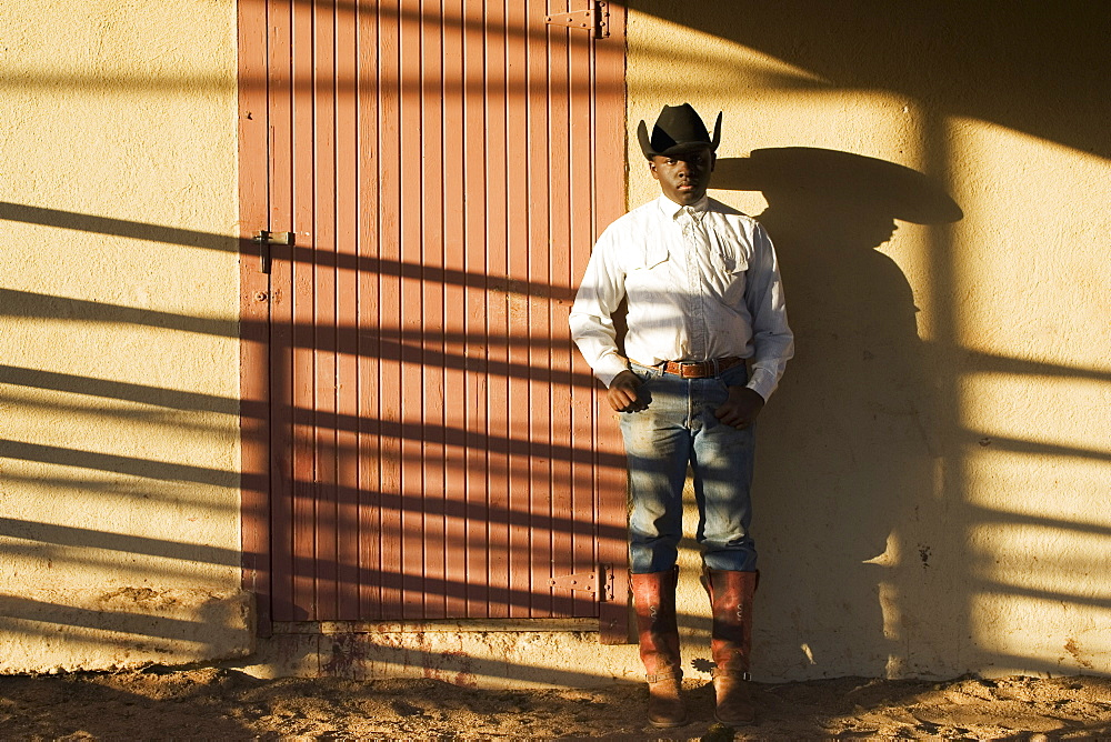 Agriculture - A young black cowboy stands against a bunkhouse wall with late afternoon shadows / Childress, Texas, USA.