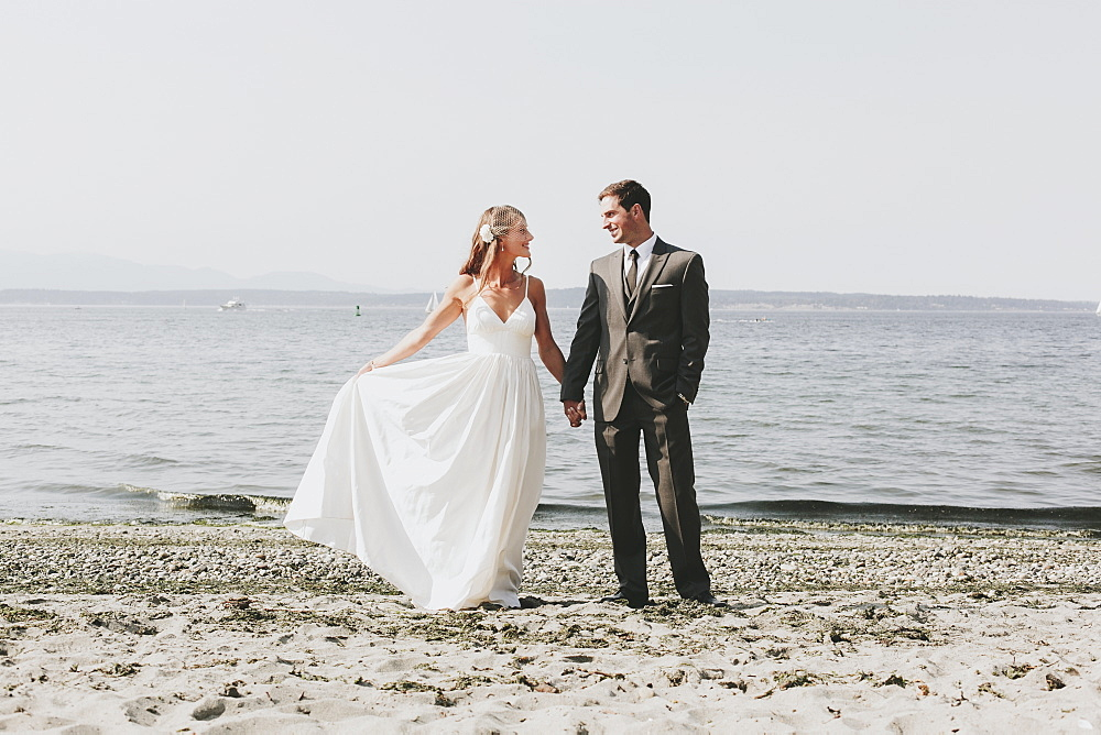 A bride and groom on a beach at the water's edge, Kirkland washington united states of america - 1116-42802