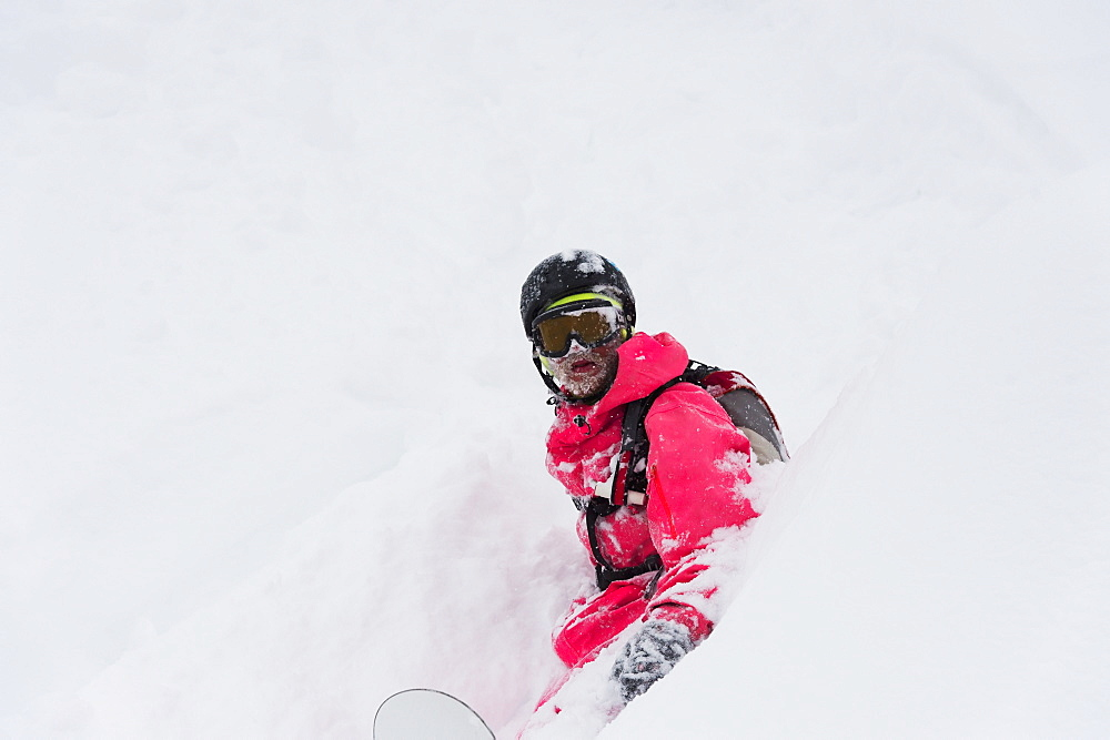 Snowboarder Sitting In Deep Powder Snow, St. Moritz, Graubunden, Switzerland