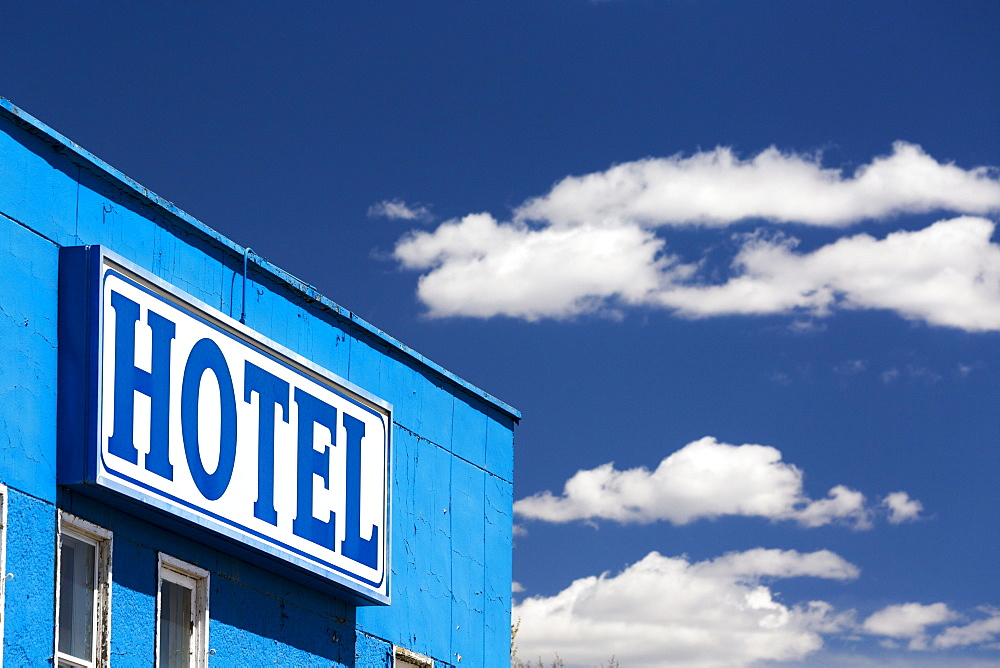Close Up Of Hotel Sign On Blue Building With Blue Sky And Clouds, Caresland, Alberta, Canada
