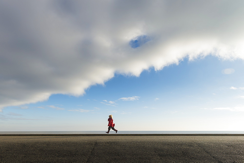 Boy Running Along Sea Wall, Aldeburgh, Suffolk, England