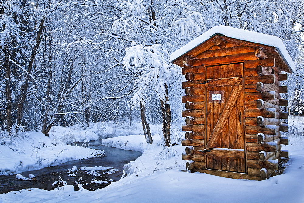 Log Outhouse By A Meandering Creek In Snow, Chena Hot Springs Resort, Fairbanks, Alaska, United States Of America