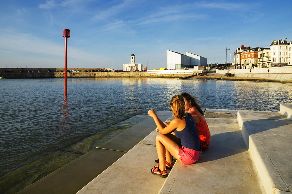 Teenage Girls Sitting On Steps Along The Waterfront, Margate, Kent, England
