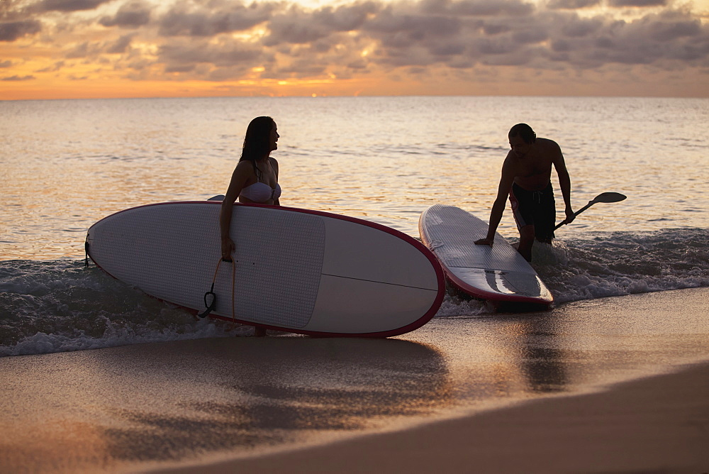 Couple Paddleboarding At Sunset, Caribbean