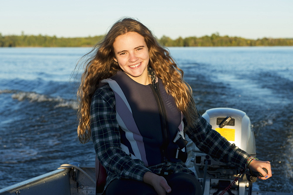 A Teenage Girl Sits By The Motor At The Back Of A Motorboat With Her Face Illuminated By Sunlight, Ontario, Canada