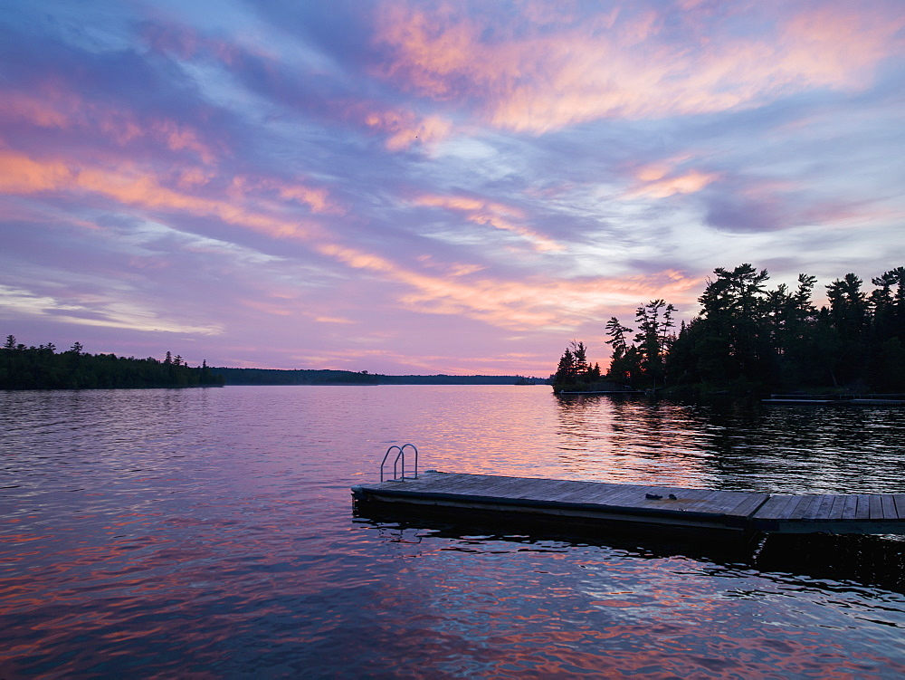 A Tranquil Lake Reflecting The Pink Clouds Of A Sunset, Ontario, Canada