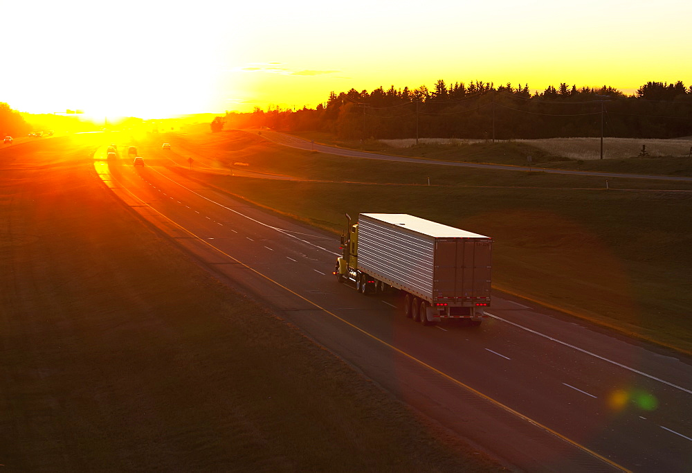 Truck Heading Down A Highway At Sunset, Edmonton, Alberta, Canada