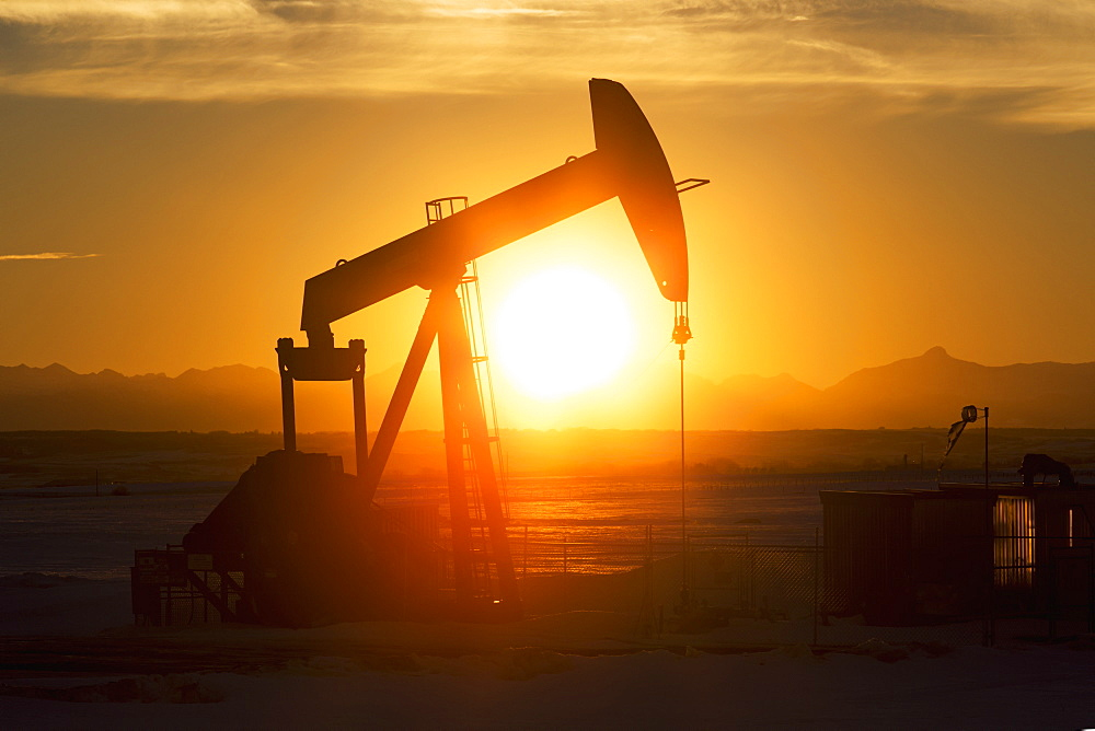 Silhouetted Pumpjack At Sunset With Mountains In The Background And Glowing Sunlight, Alberta, Canada