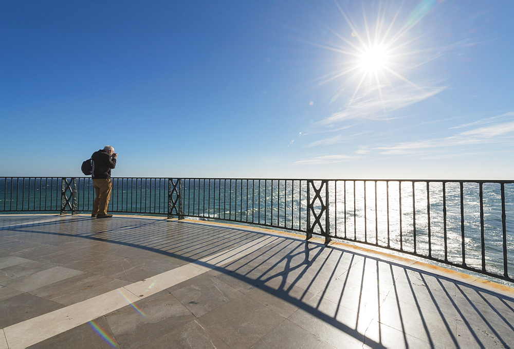 A Man Stands Taking A Photograph At The Railing Along The Water's Edge, Nerja, Malaga, Costa Del Sol, Andalusia, Spain