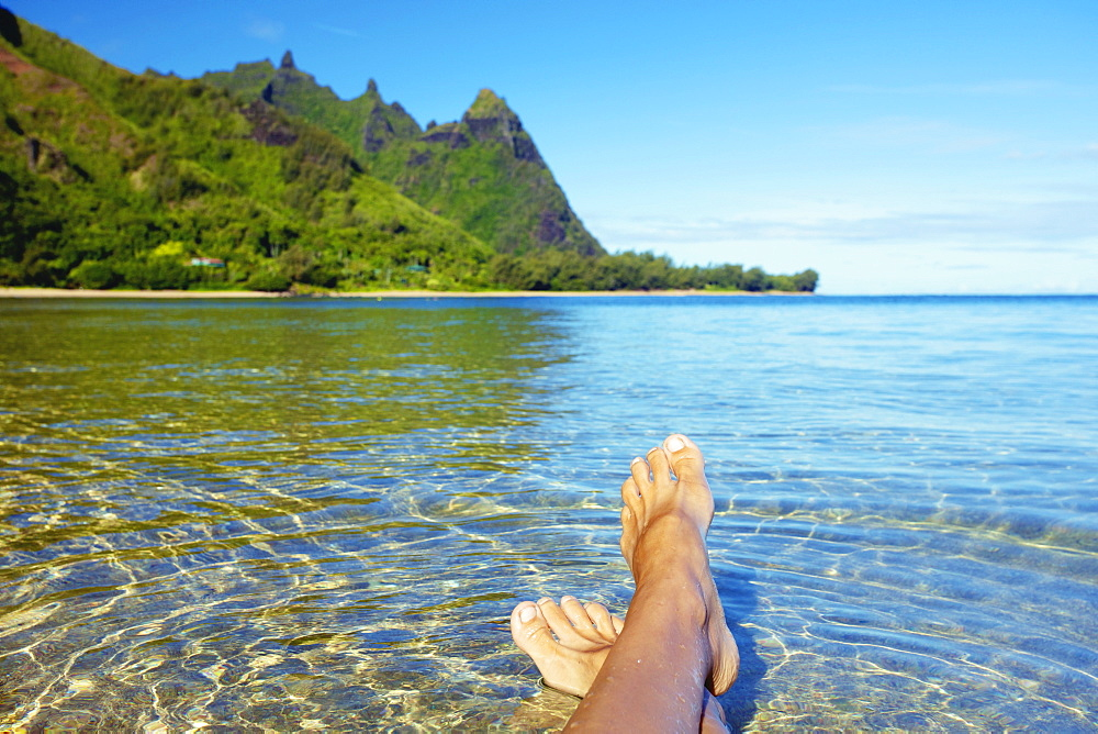 Bare Feet In The Clear Shallow Water Along The Coast Of An Hawaiian Island, Kauai, Hawaii, United States Of America