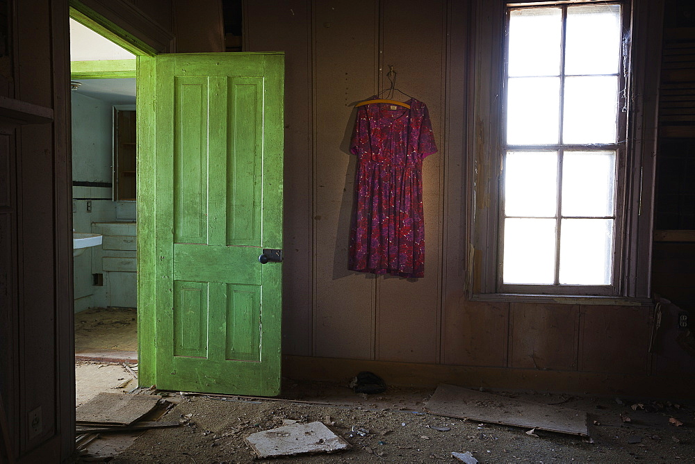 Room Inside An Old Abandoned House With A Green Door Open And An Old Dress Hanging On The Wall, United States Of America