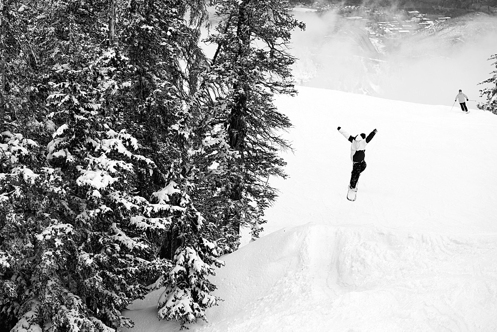 Person In Air After Making A Jump While Snowboarding, Aspen, Colorado, USA