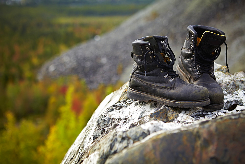 Work Boots On A Rock With Autumn Coloured Trees In The Background, Quebec, Canada