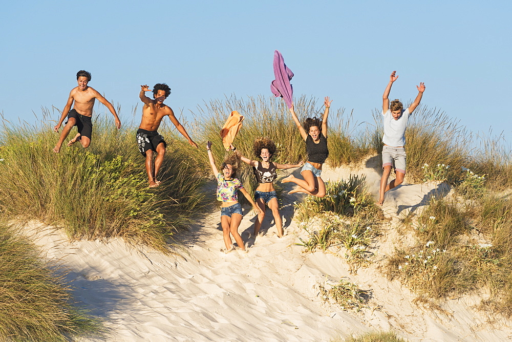 A Group Of Teenagers Running And Jumping Over Sand And Beach Grass, Tarifa, Cadiz, Andalusia, Spain