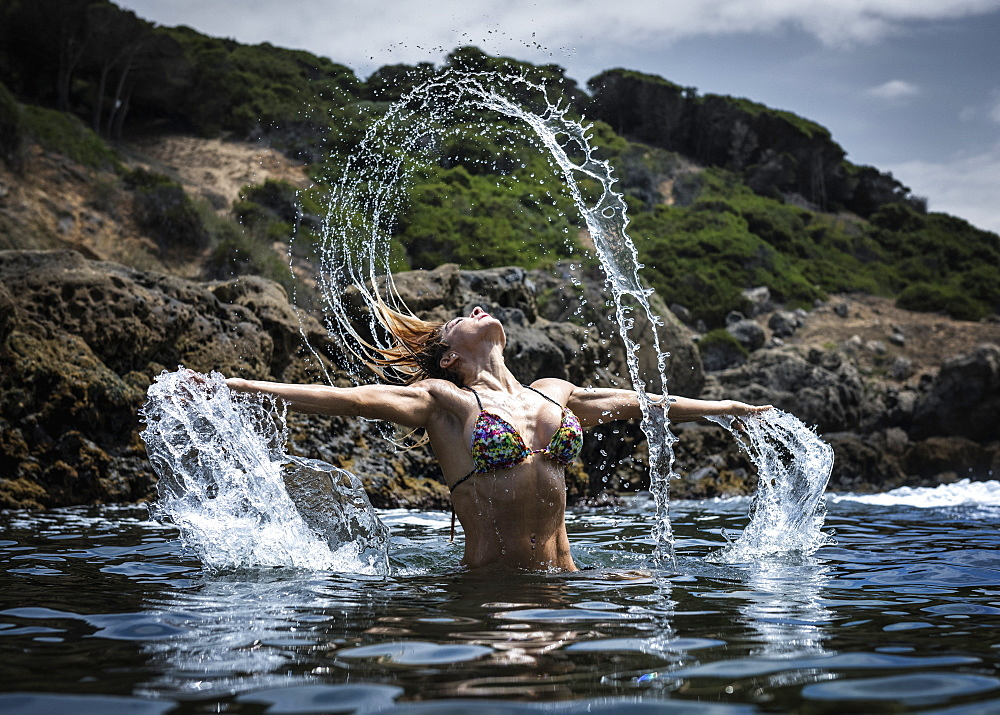 A Young Woman In A Bikini Splashing Water Along The Water's Edge, Tarifa, Cadiz, Andalusia, Spain