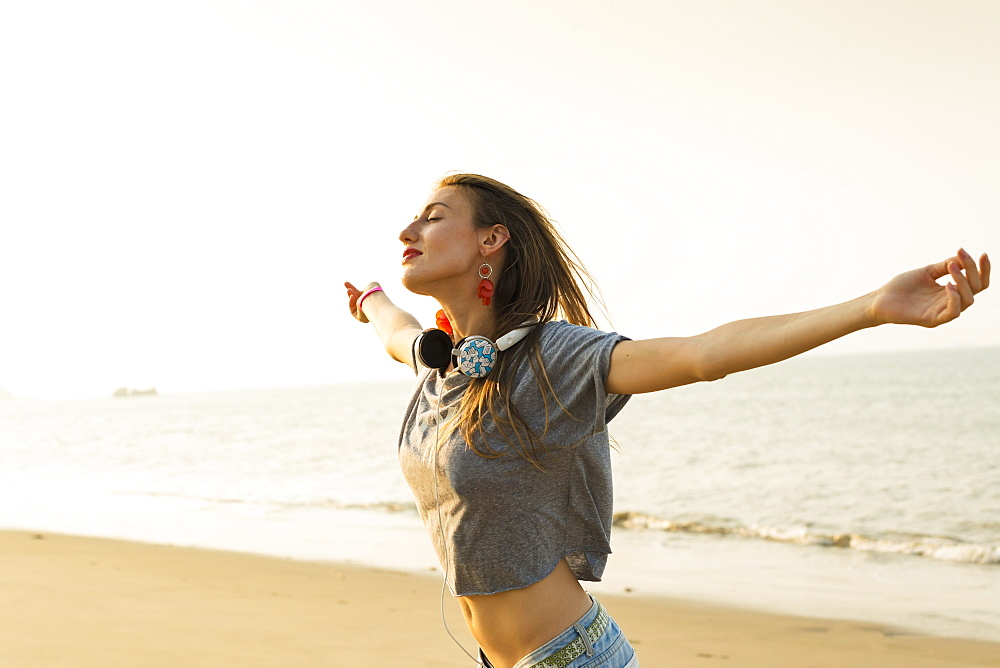 Young Woman Listening To Music With Her Headphones On The Beach, Xiamen, China