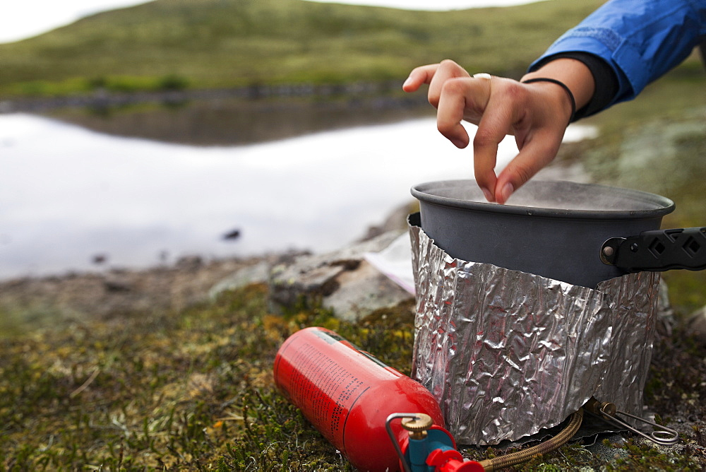 Female Backpacker Cooks With A Backpacker Camp Stove Near The Edge Of A Lake, Alaska