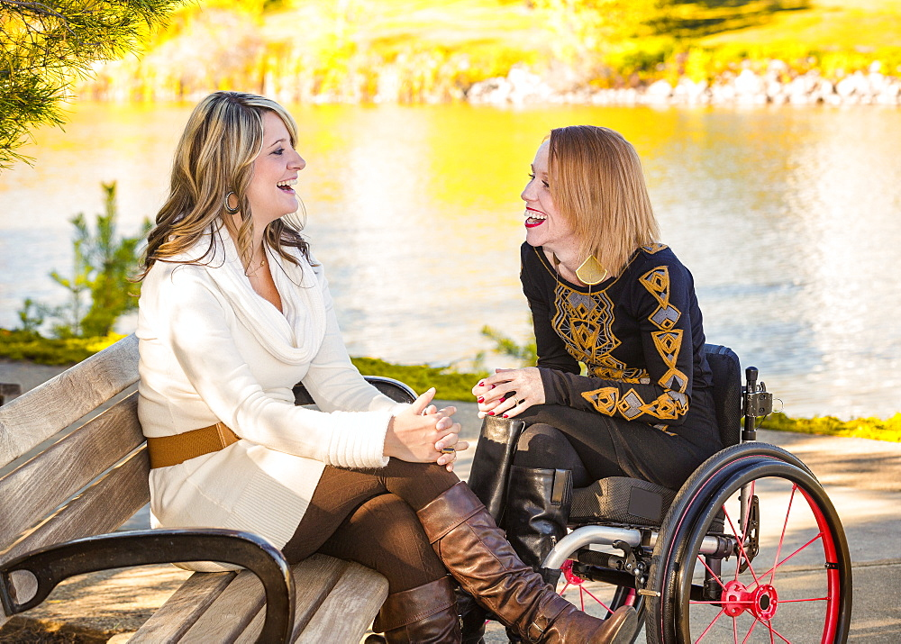 Young Paraplegic Woman And Her Friend Spending Quality Time Together In A City Park In Autumn, Edmonton, Alberta, Canada