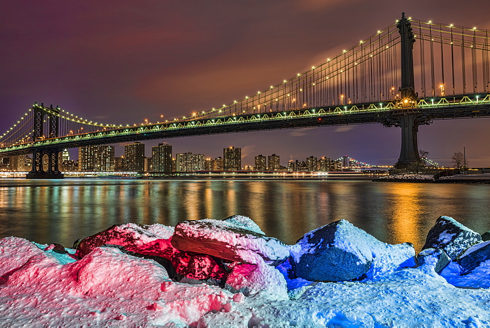 Manhattan Bridge By Snow-Covered Rocks At Sunset, Brooklyn Bridge Park, Brooklyn, New York, United States Of America