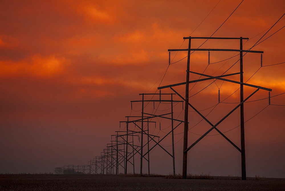 Power Lines At Sunset With Glowing Orange Sky, Saskatchewan, Canada