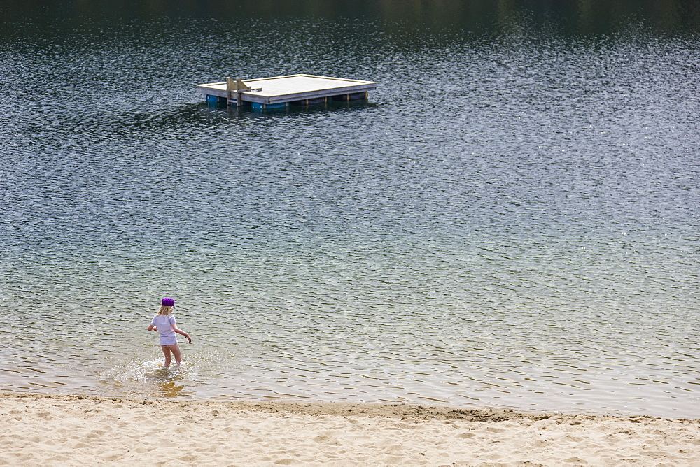 A Young Girl Plays In The Water Along A Sandy Beach, Lucky Lake, Yukon Territory, Canada, Summer