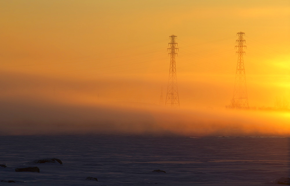 Electricity Pylons In The Fog At Sunrise On The Shore Of The St. Lawrence River, Les Cedres, Quebec, Canada