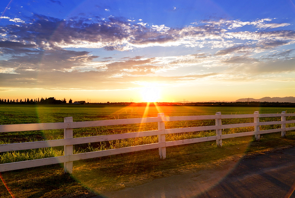 Sunlight Shining Across A Grass Field And White Rail Fence At Sunset, British Columbia, Canada