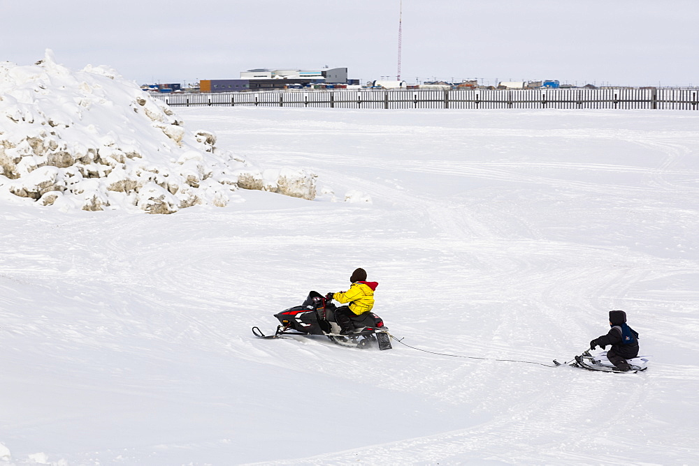 Native Alaskan Youth On A Snowmachine Towing Another On Sled, City Of Barrow In The Background, North Slope, Arctic Alaska, USA, Winter