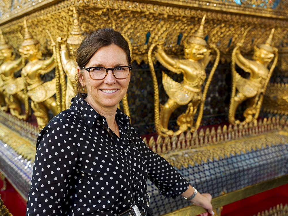 Portrait Of A Woman Standing Beside A Wall With Gold Statues, Temple Of The Emerald Buddha (Wat Phra Kaew), Bangkok, Thailand