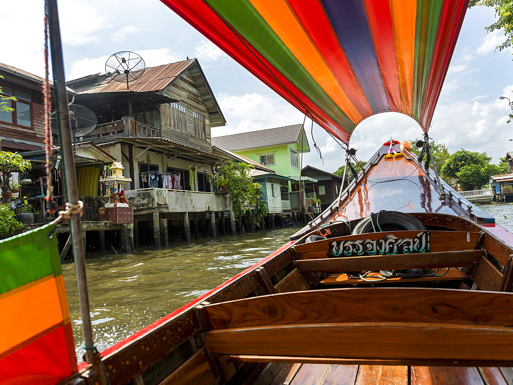 A Boat On The River With A Colourful Cover And Houses Along The Shoreline, Bangkok, Thailand