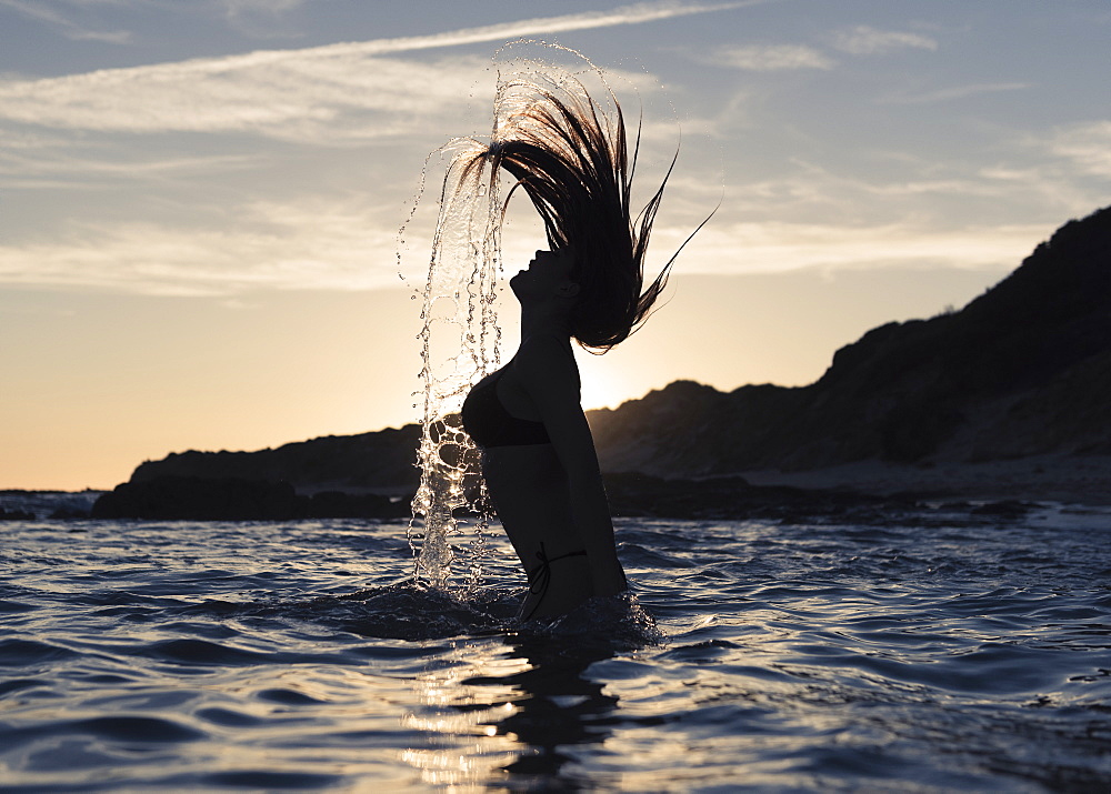 Silhouette Of A Woman In Waist-Deep Water Flipping Her Wet Long Hair Up In The Air, Tarifa, Cadiz, Andalusia, Spain