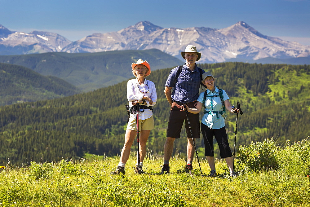 Three Hikers, Two Female And One Male, On Top Of Grassy Hill With Rolling Foothills And Mountain Range In The Background With Blue Sky, Kananaskis Country, Alberta, Canada