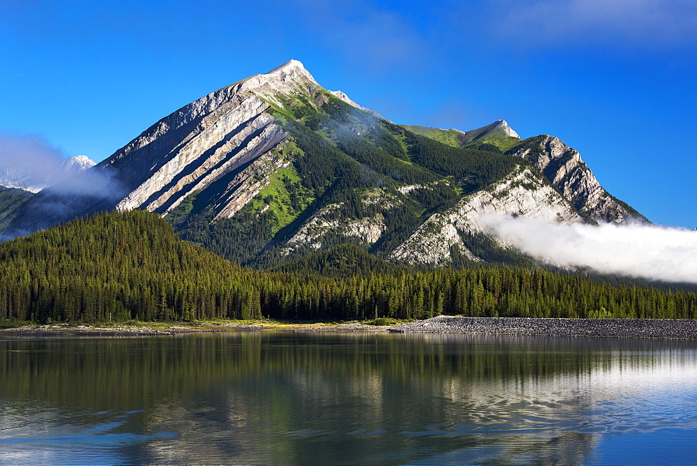 Mountain Reflecting In Lake With Fog Patches And Blue Sky, Kananaskis Country, Alberta, Canada