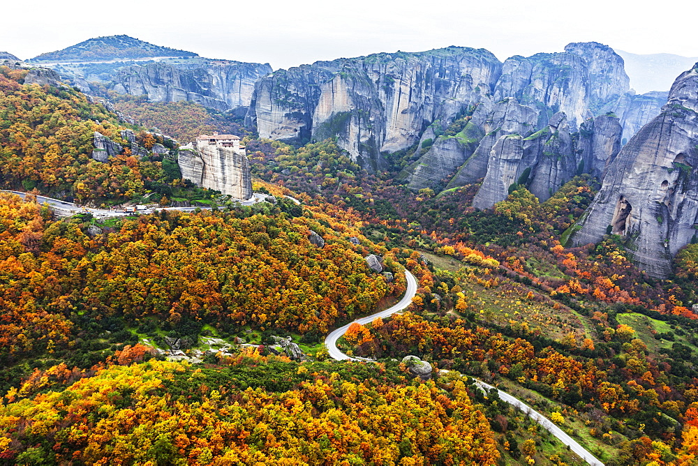 Monastery Perched On A Cliff With Autumn Coloured Foliage, Meteora, Greece