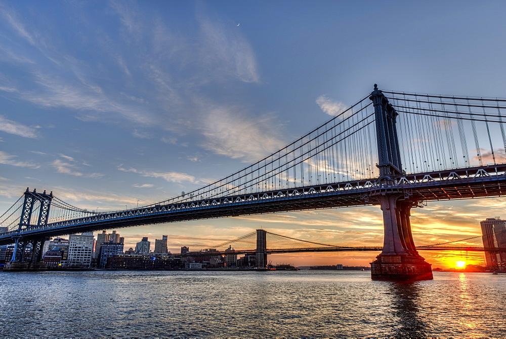 Sun Setting Behind Manhattan And Brooklyn Bridges, New York City, New York, United States Of America