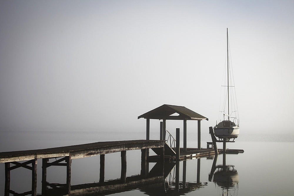 Sailboat On Lift By Dock On Foggy Lake, Bellingham, Washington, United States Of America