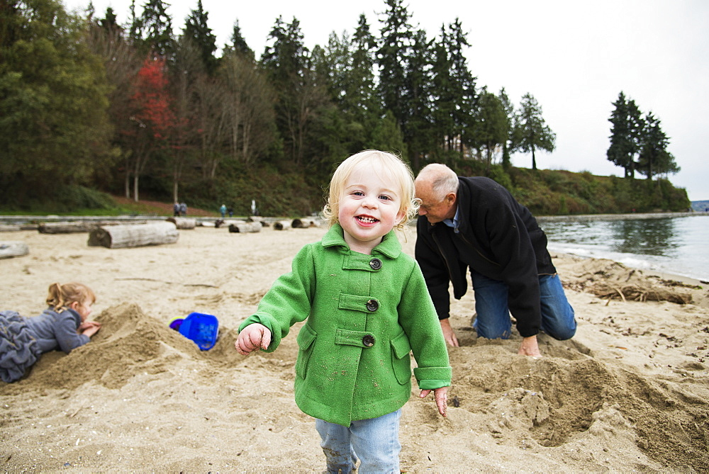 A Young Girl Walks Towards The Camera While A Grandfather And Granddaughter Play In The Background On The Beach In Winter At Stanley Park, Vancouver, British Columbia, Canada
