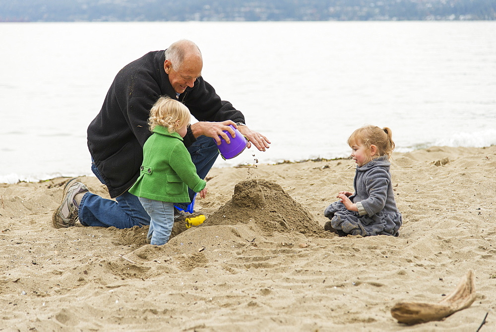 In Cold Weather, A Grandfather Plays With His Two Grand-Daughters On The Beach At Stanley Park, Vancouver, British Columbia, Canada